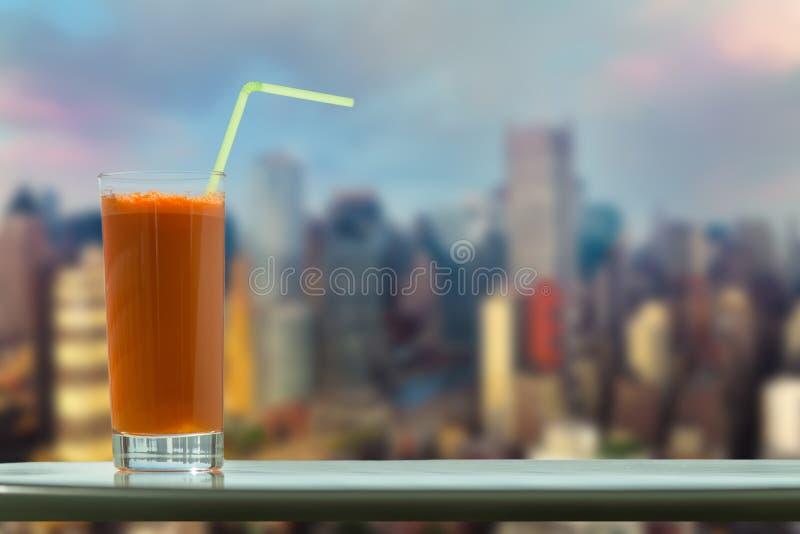Un vidrio de jugo de zanahoria con una paja en el café en el fondo Manhattan New York City imagen de archivo libre de regalías
