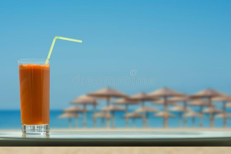 Un vidrio de jugo de zanahoria con una paja en el café en los fondos tropicales de la playa fotografía de archivo libre de regalías