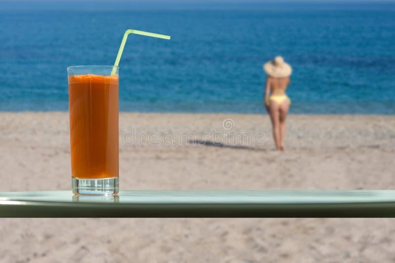 Un vidrio de jugo de zanahoria con una paja en el café Una muchacha distante en bikini y un sombrero de paja en una playa fotografía de archivo libre de regalías