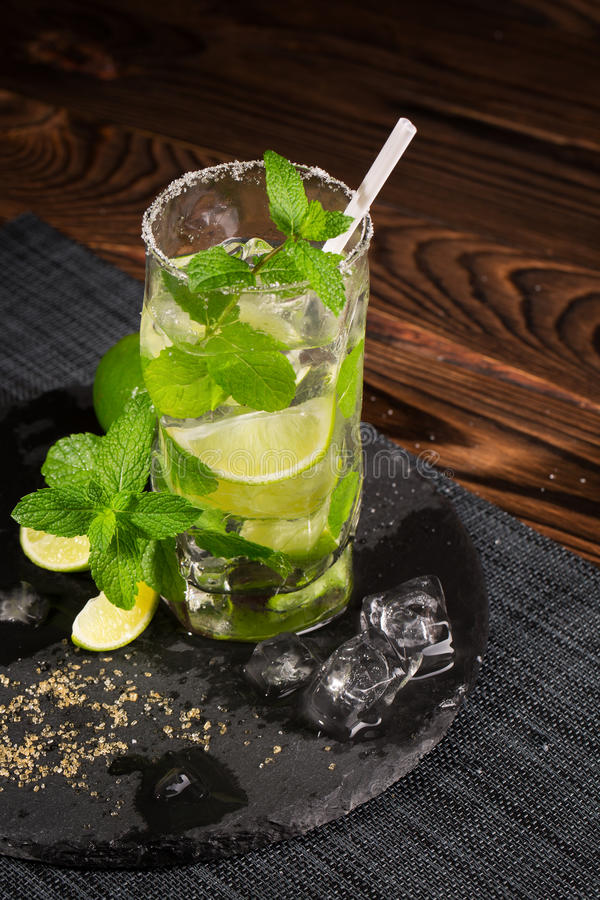 Un vidrio de la bebida del alcohol de la cal jugosa, del ron, de la menta fresca y del hielo machacado en un fondo de madera oscu foto de archivo