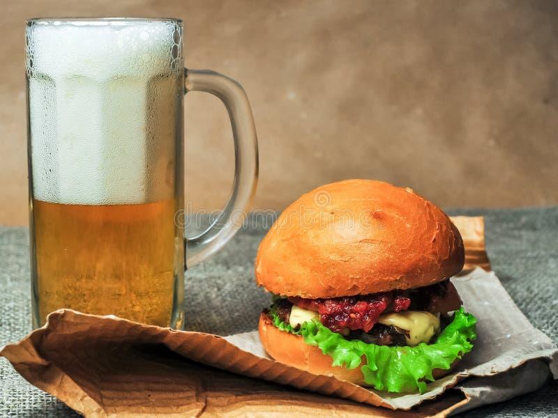 Un vidrio de la cerveza y de un cheeseburger en un papel del arte foto de archivo
