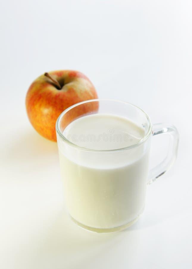 Un vidrio de la leche y de la manzana imagen de archivo