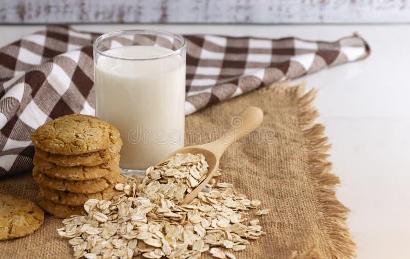 Un vidrio de leche, de galletas, y de avena en cuchara en la tabla de madera Su son una comida alimento-rica asociada a la proteí foto de archivo libre de regalías