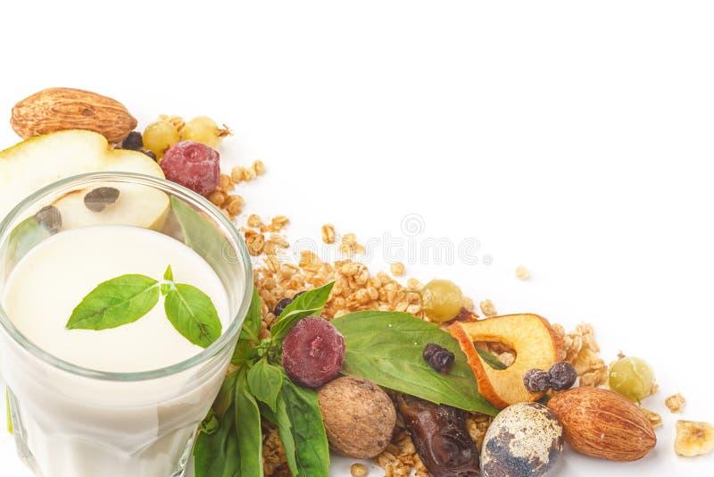 Un vidrio de leche y de muesli con las frutas y las hierbas en un fondo blanco Aislado imagen de archivo