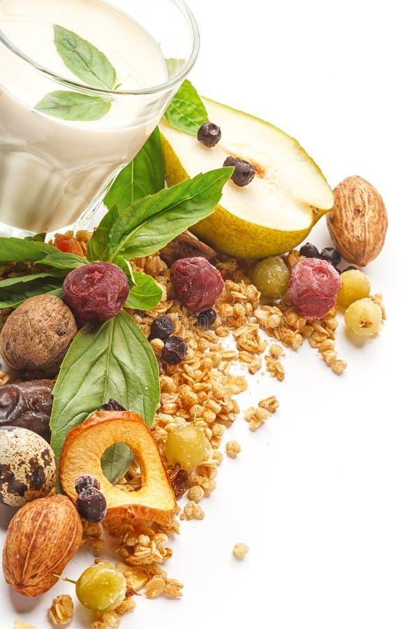 Un vidrio de leche y de muesli con las frutas y las hierbas en un fondo blanco Aislado imagen de archivo libre de regalías