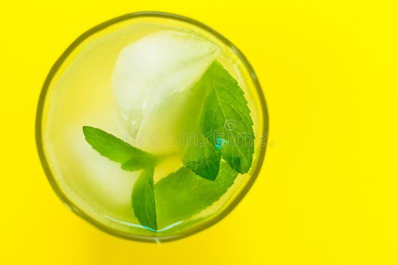 Un vidrio de limonada con la menta en un fondo amarillo brillante Bebida de enfriamiento Visi?n desde arriba imagen de archivo