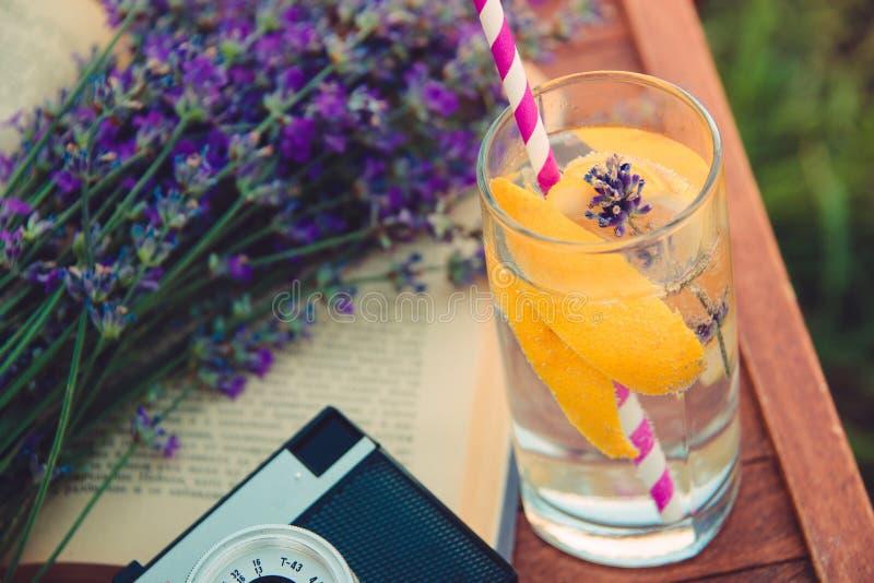 Un vidrio de limonada de restauración, de cameta del vintage, de un libro y de lavanda recientemente cutted florece sobre una sil foto de archivo libre de regalías