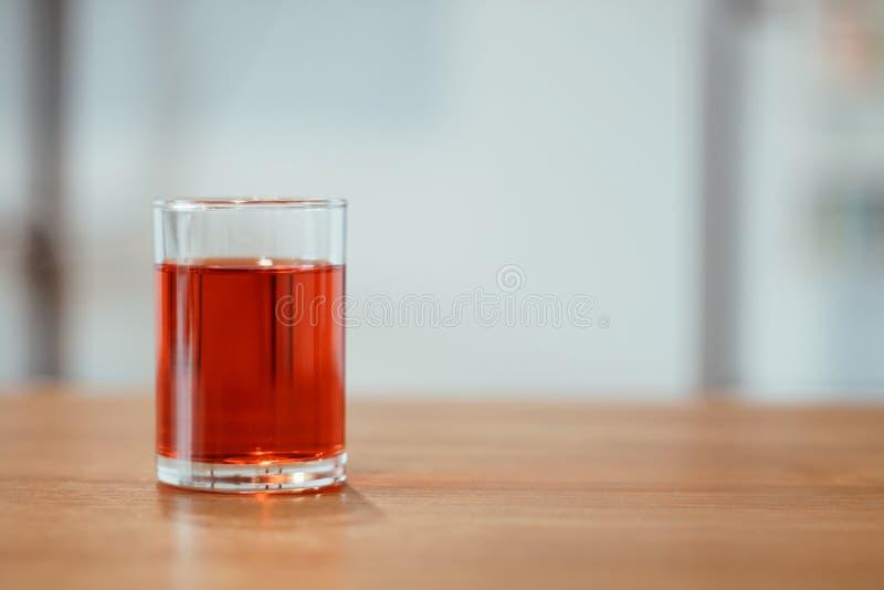 Un vidrio de soda roja dulce en la tabla imagen de archivo libre de regalías