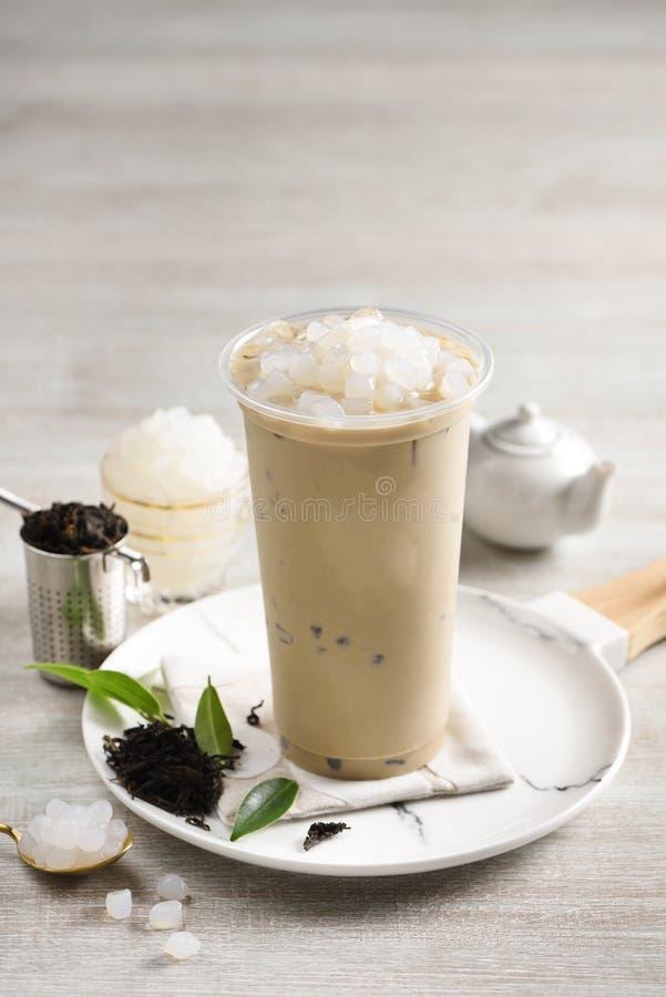 Un vidrio de té de la leche All? un poco de cal cortada en la placa y un peque?o pote del t? verde imagen de archivo