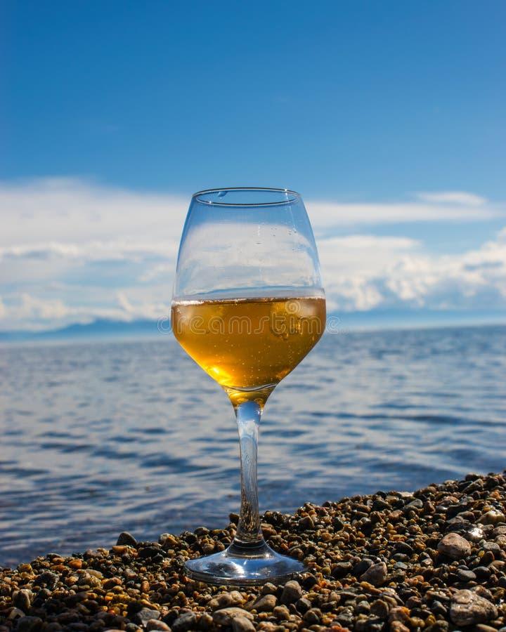 Un vidrio de vino blanco con los cubos de hielo en la orilla de Ozen contra el cielo imagen de archivo libre de regalías