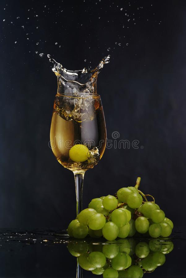 Un vidrio de vino blanco en un fondo oscuro Vino blanco del chapoteo Manojo de la uva imagenes de archivo