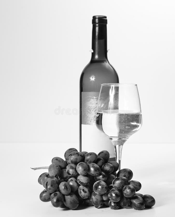 Un vidrio de vino blanco, un manojo de uvas, una botella abierta fotografía de archivo
