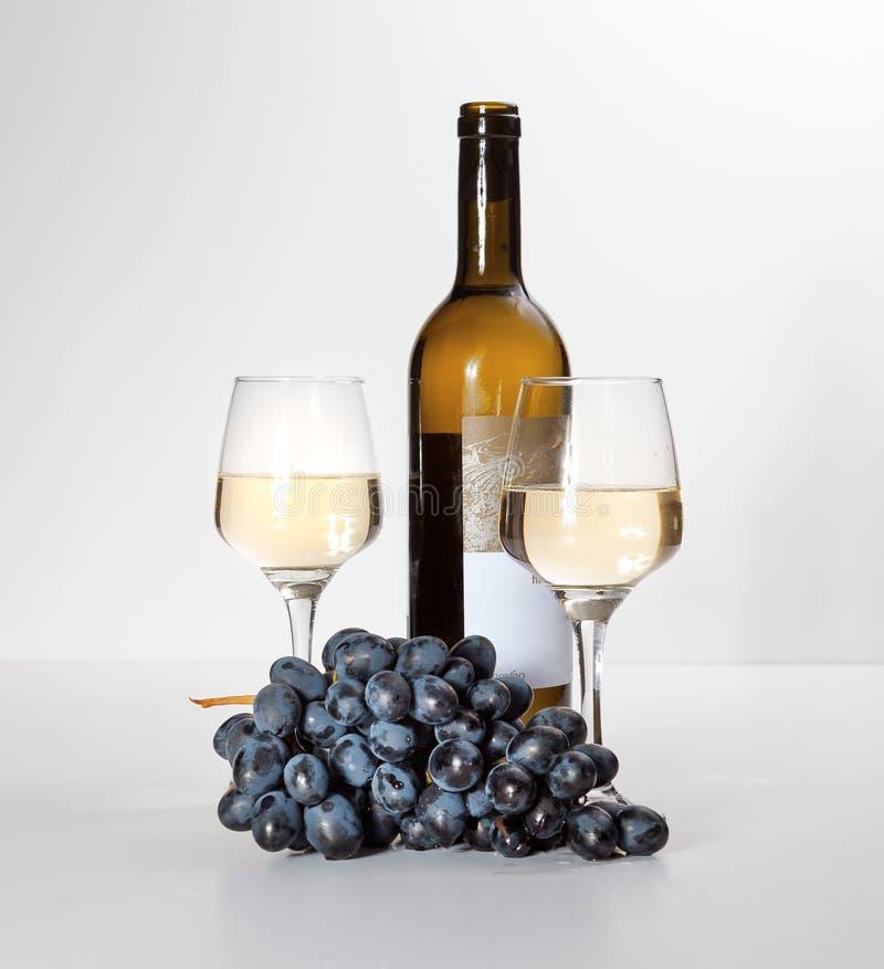 Un vidrio de vino blanco, un manojo de uvas, una botella abierta fotos de archivo libres de regalías
