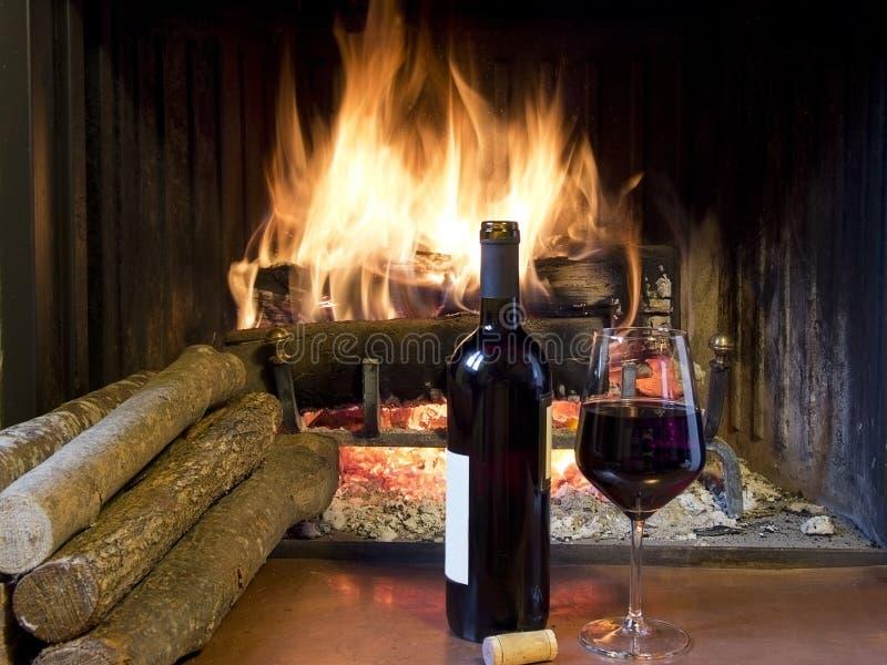 Un vidrio de vino delante de una chimenea imagen de archivo libre de regalías