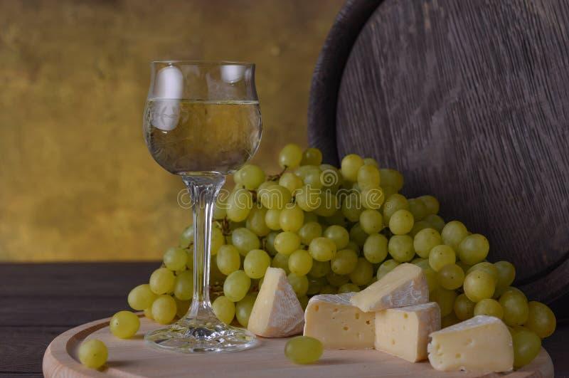 Un vidrio de vino en el fondo de las uvas blancas, del queso y de los barriles en una tabla de madera foto de archivo