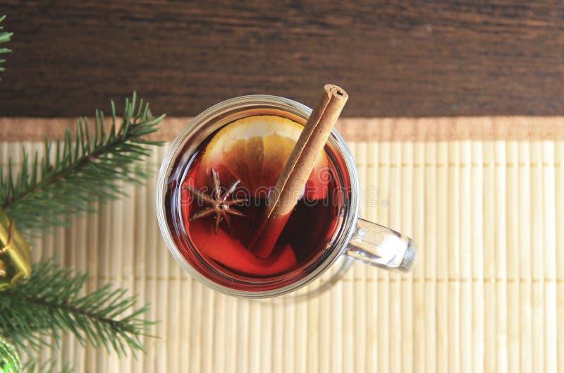 Un vidrio de vino reflexionado sobre está en una servilleta de bambú Una puntilla del acebo Bebida del ` s del Año Nuevo fotografía de archivo libre de regalías