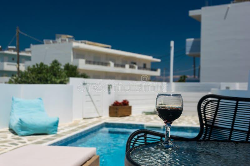 Un vidrio de vino tinto en la tabla por la piscina imagen de archivo libre de regalías