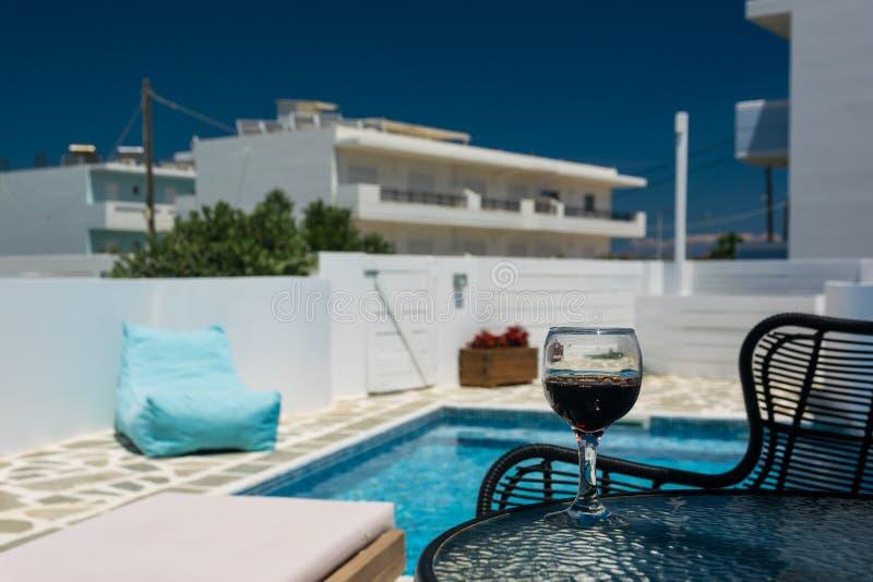 Un vidrio de vino tinto en la tabla por la piscina fotografía de archivo
