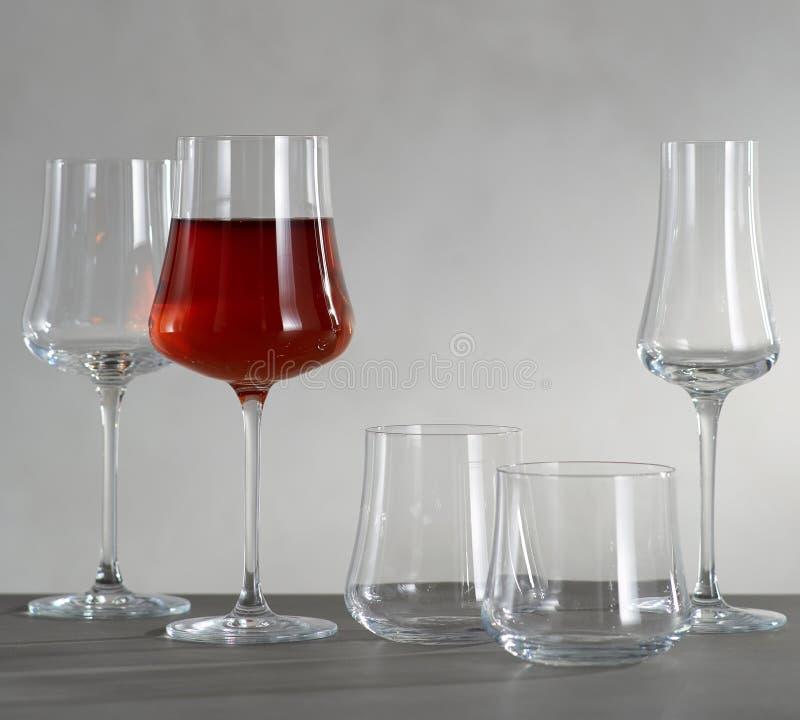 Un vidrio de vino tinto y de cuatro copas de vino vacías imagenes de archivo