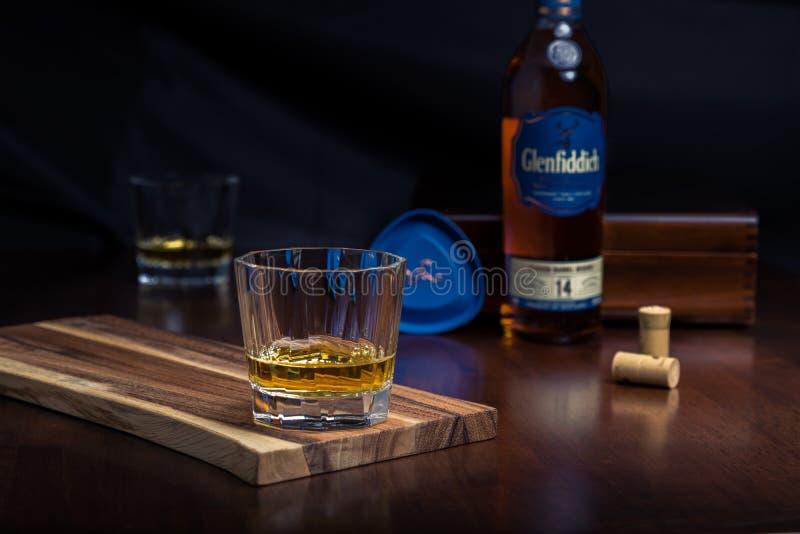 Un vidrio de whisky en una sobremesa del palo de rosa foto de archivo libre de regalías