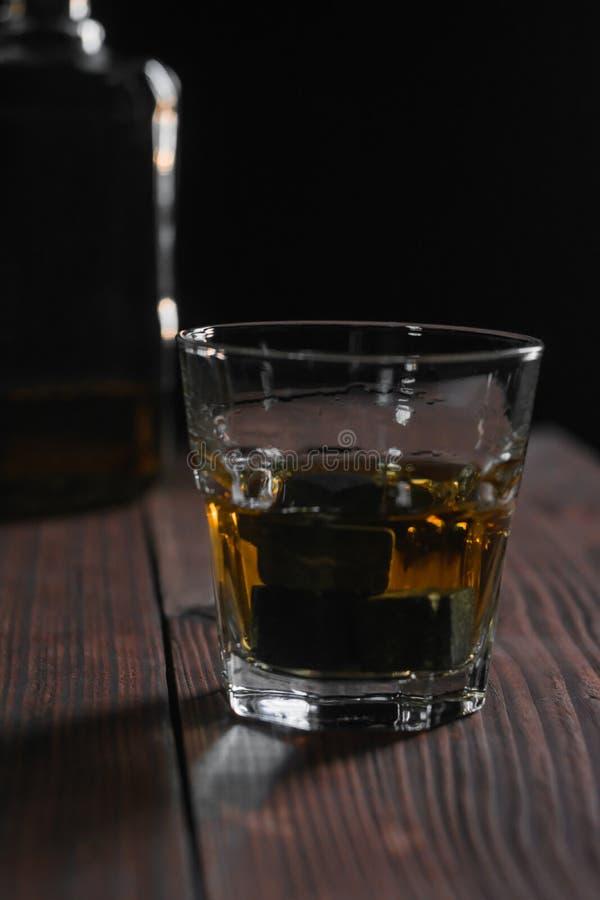 Un vidrio de whisky y de piedras que se colocan en el primero plano en una tabla de madera En el fondo es un frag imagenes de archivo