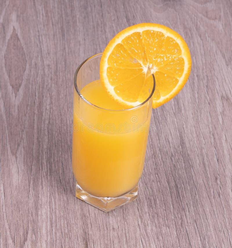 Un vidrio de zumo de naranja con una rebanada de naranja en un fondo texturizado de madera foto de archivo