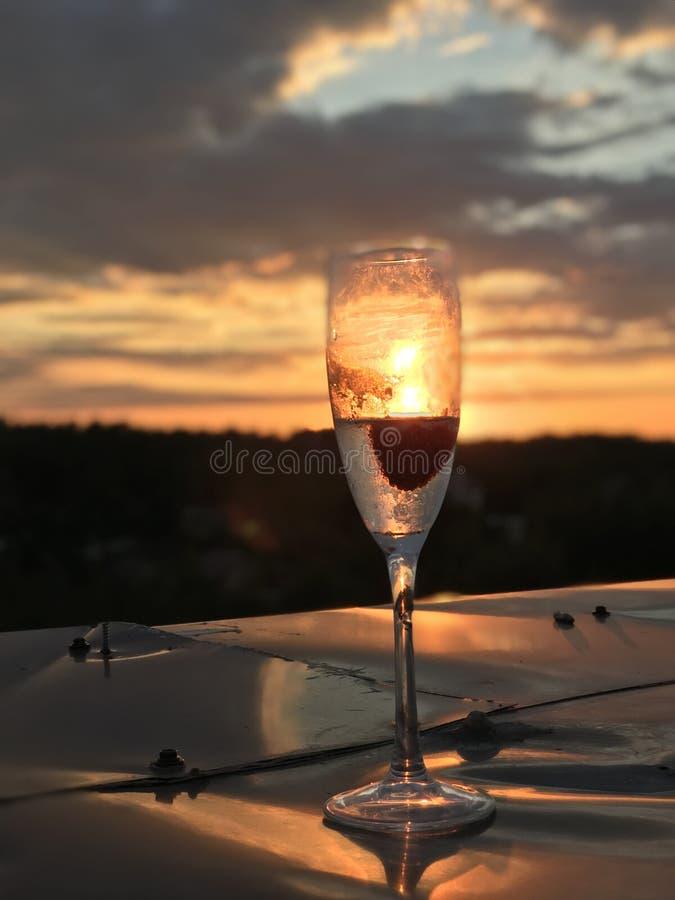 Un vidrio del champán delante de una puesta del sol caliente lleva a cabo una fresa y una ráfaga enfriada de rieseling fotos de archivo