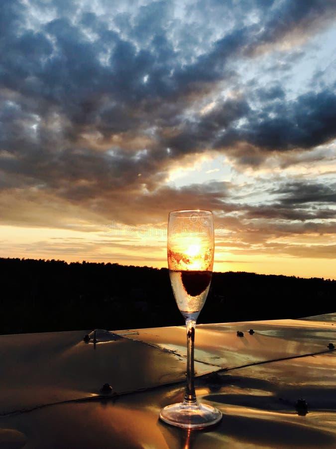 Un vidrio del champán lleva a cabo una fresa y una ráfaga enfriada de rieseling fotografía de archivo