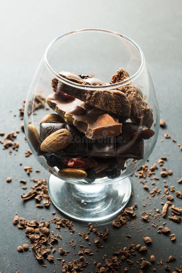Un vidrio del chocolate en un fondo negro, migas del chocolate imagen de archivo