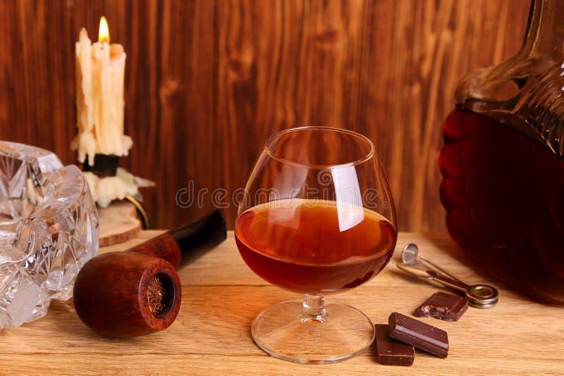 Un vidrio del coñac, del chocolate y del tubo que fuma fotografía de archivo libre de regalías