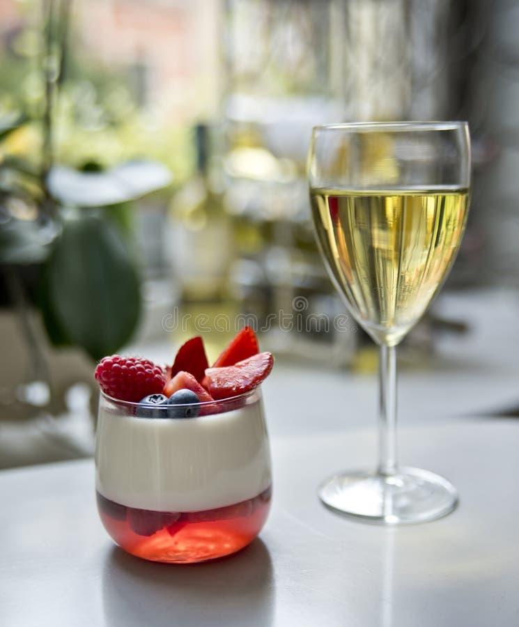 Un vidrio del vino blanco y de un postre del panakota imagen de archivo