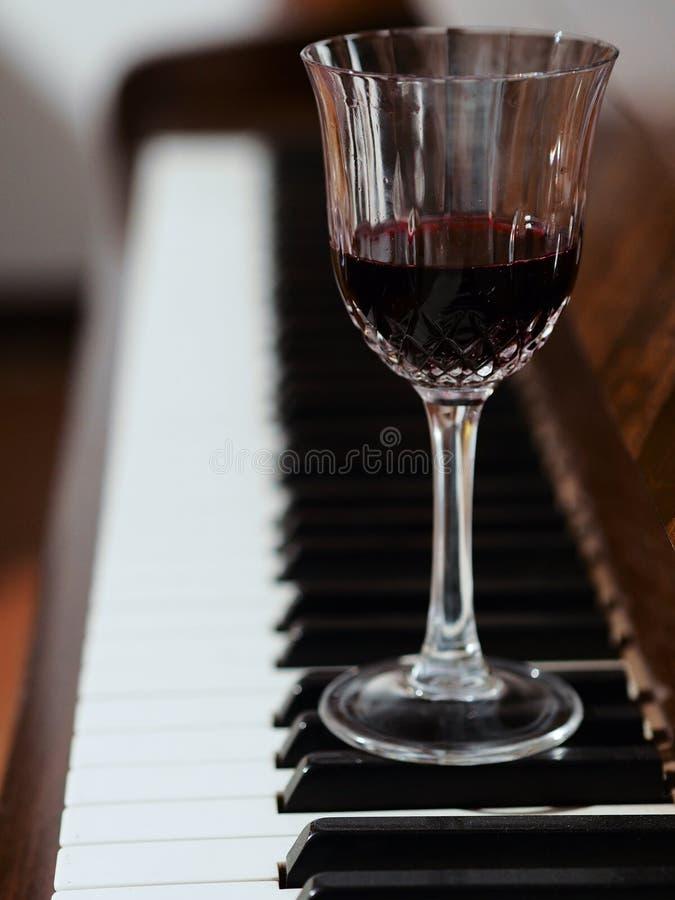 Un vidrio del vino rojo y del piano foto de archivo