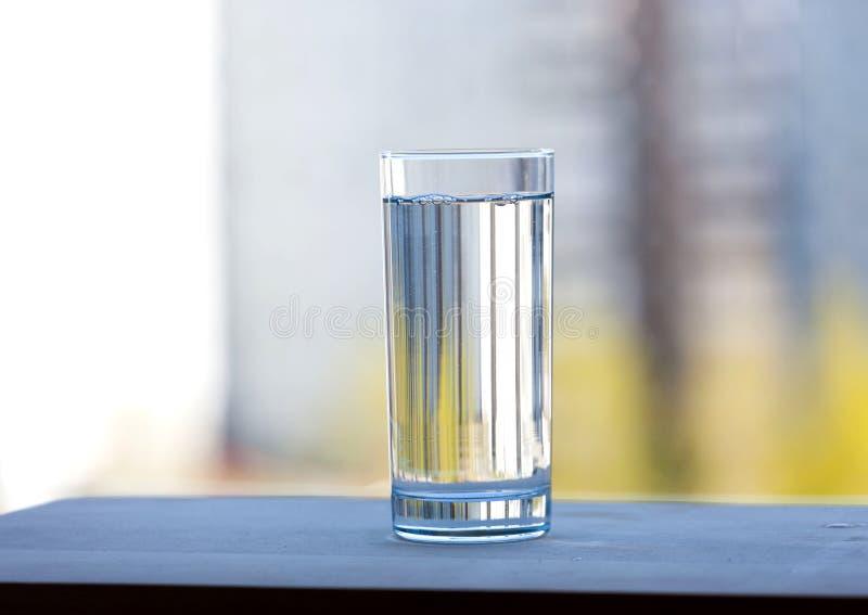 Un vidrio lleno de agua potable al aire libre Día asoleado del verano foto de archivo