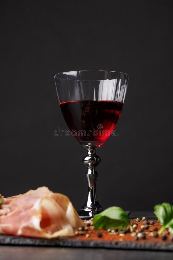 Un vidrio transparente de vino rojo y una pila de jamón cortado en un fondo negro Prosciutto sabroso, albahaca verde picante y imagen de archivo libre de regalías