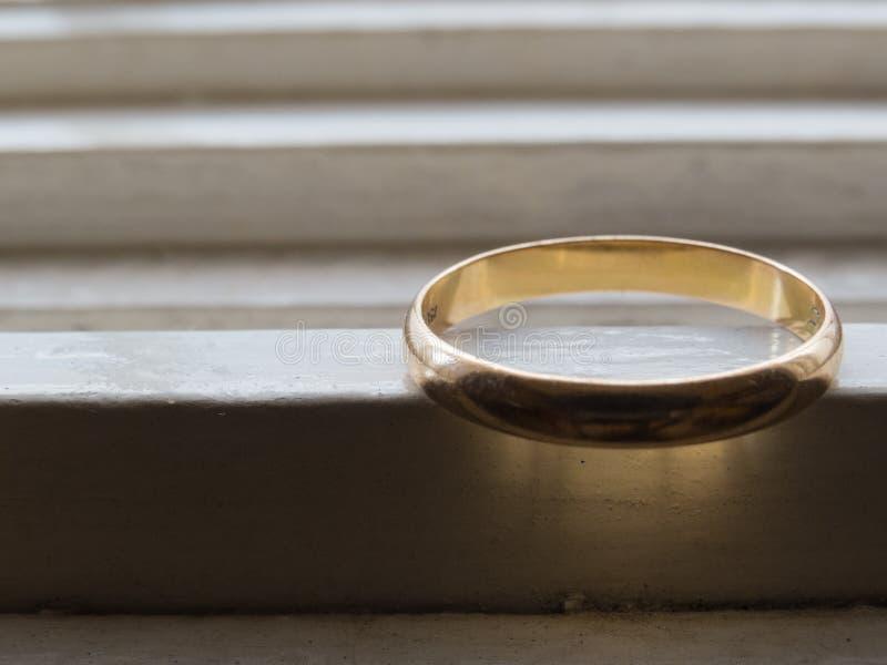 Un vieil anneau de mariage en or, sur une étagère blanche image libre de droits