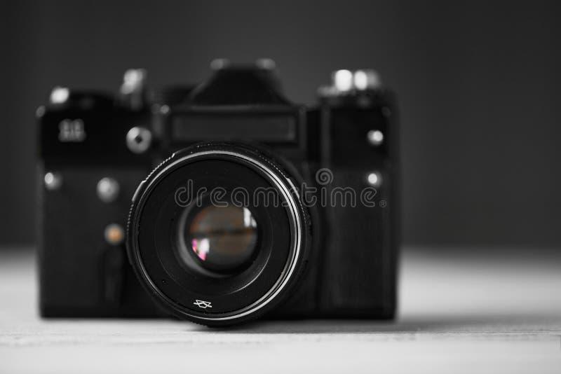 Un vieil appareil-photo de noir de vintage, un instrument optique pour enregistrer ou saisir des images sur un fond en bois broui photo libre de droits