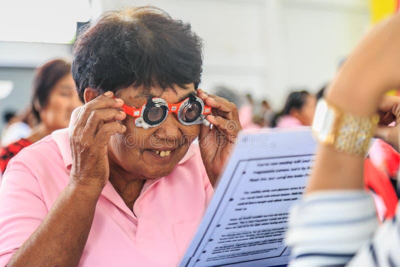 Un vieil essai de femme de l'Asie observe des cadres d'essai images stock