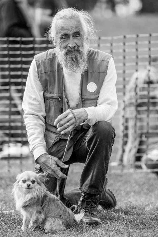 Un vieil homme avec son chien en parc à une exposition canine à Londres photo libre de droits