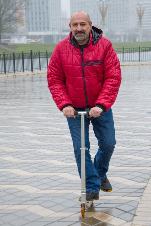 Un vieil homme chauve à la barbe fait une balade en scooter sur la promenade de la ville dans la métropole Un mode de vie sain en photographie stock libre de droits