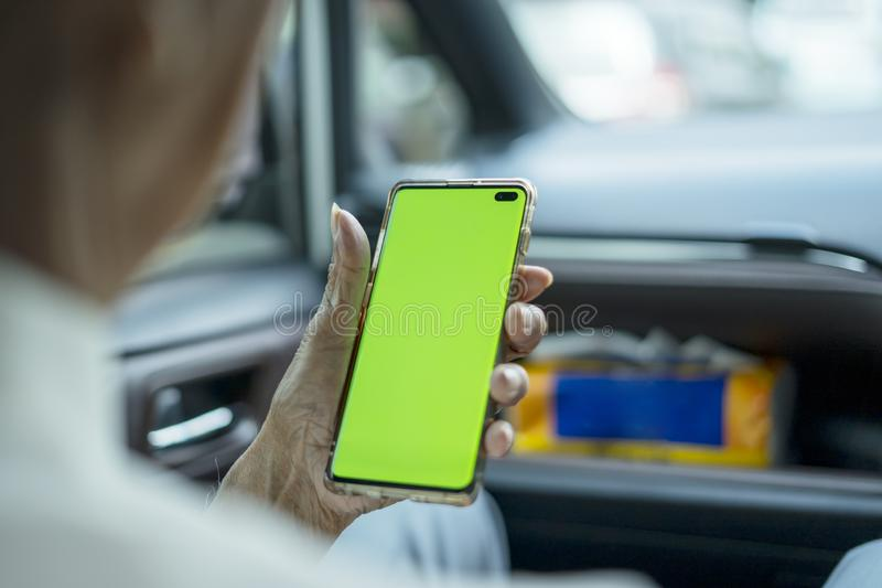 Un vieil homme utilisant un téléphone avec écran vierge dans sa voiture photographie stock libre de droits