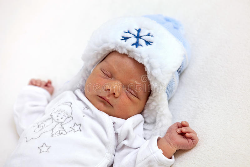 Un viejo bebé de la semana en el sombrero del invierno dormido imagenes de archivo