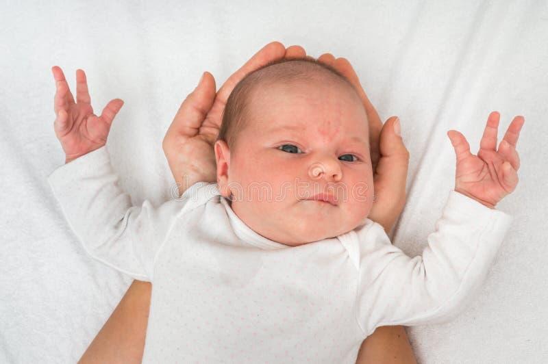 Un viejo bebé recién nacido del mes está mintiendo en las manos de la madre fotos de archivo libres de regalías