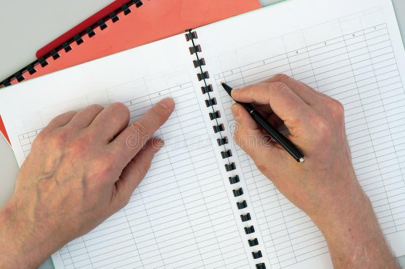 Un viejo contable completa cuidadosamente expedientes y registros de impuesto foto de archivo