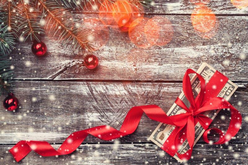 Un viejo fondo de madera de la Navidad, un árbol de abeto con las chucherías, dinero embellecido con la holgura roja imagen de archivo