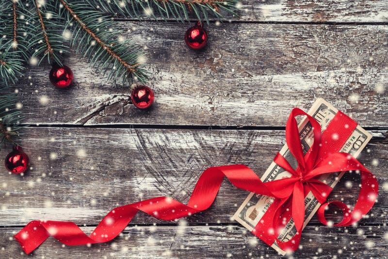 Un viejo fondo de madera de la Navidad, un árbol de abeto con las chucherías, dinero embellecido con la holgura roja Copos de nie fotografía de archivo