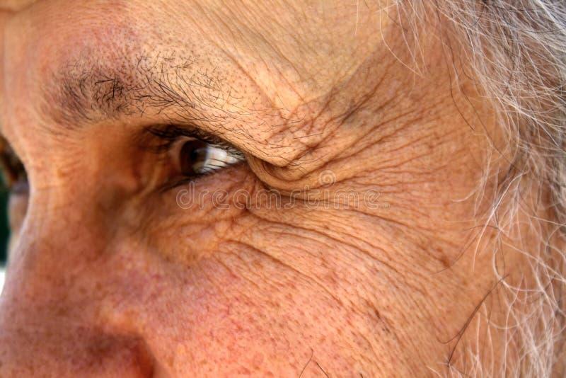 Un viejo hombre con las arrugas profundas cerca de los ojos mira en la distancia foto de archivo
