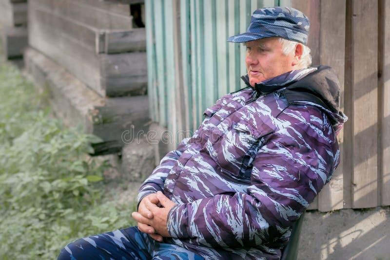 Un viejo hombre en ropa del camuflaje se está sentando en una silla al aire libre El concepto de trabajo como guardia de segurida fotos de archivo libres de regalías