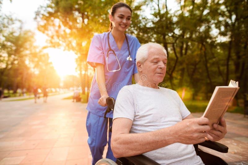 Un viejo hombre que se sienta en una silla de ruedas y una enfermera que se esté colocando detrás de él que lee un libro en el pa imagen de archivo