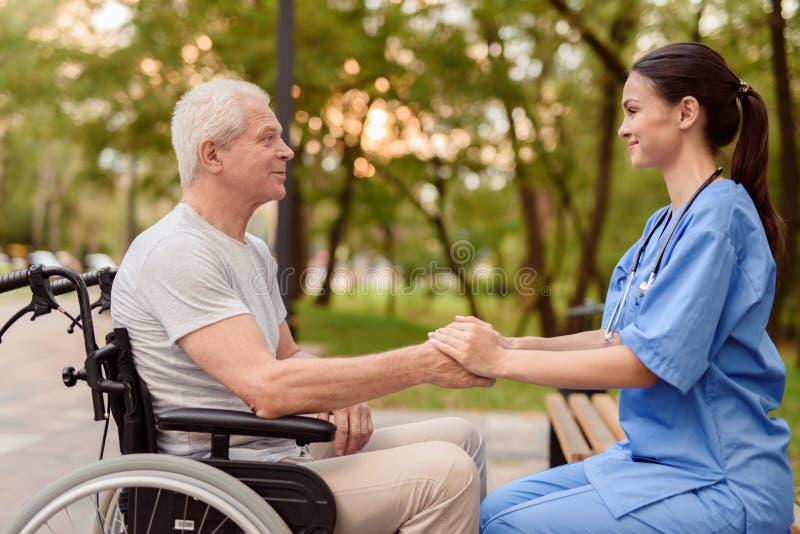 Un viejo hombre que se sienta en una silla de ruedas y una enfermera que se siente al lado del banco que lleva a cabo las manos fotografía de archivo libre de regalías