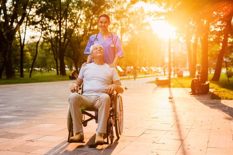 Un viejo hombre que se sienta en una silla de ruedas y un soporte de la enfermera en el parque en la puesta del sol imagen de archivo libre de regalías